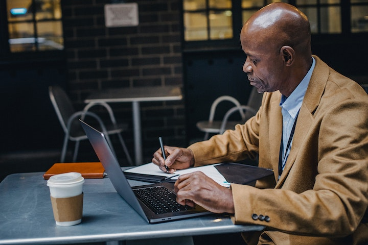 Image of a man studying on a laptop in a cafe.