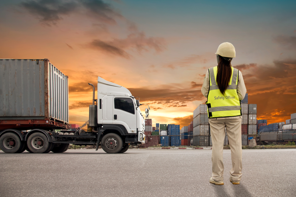 woman standing next to truck and shipping containers